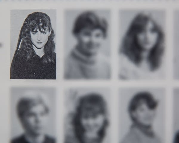 A blurred yearbook shows one person looking at the camera.
