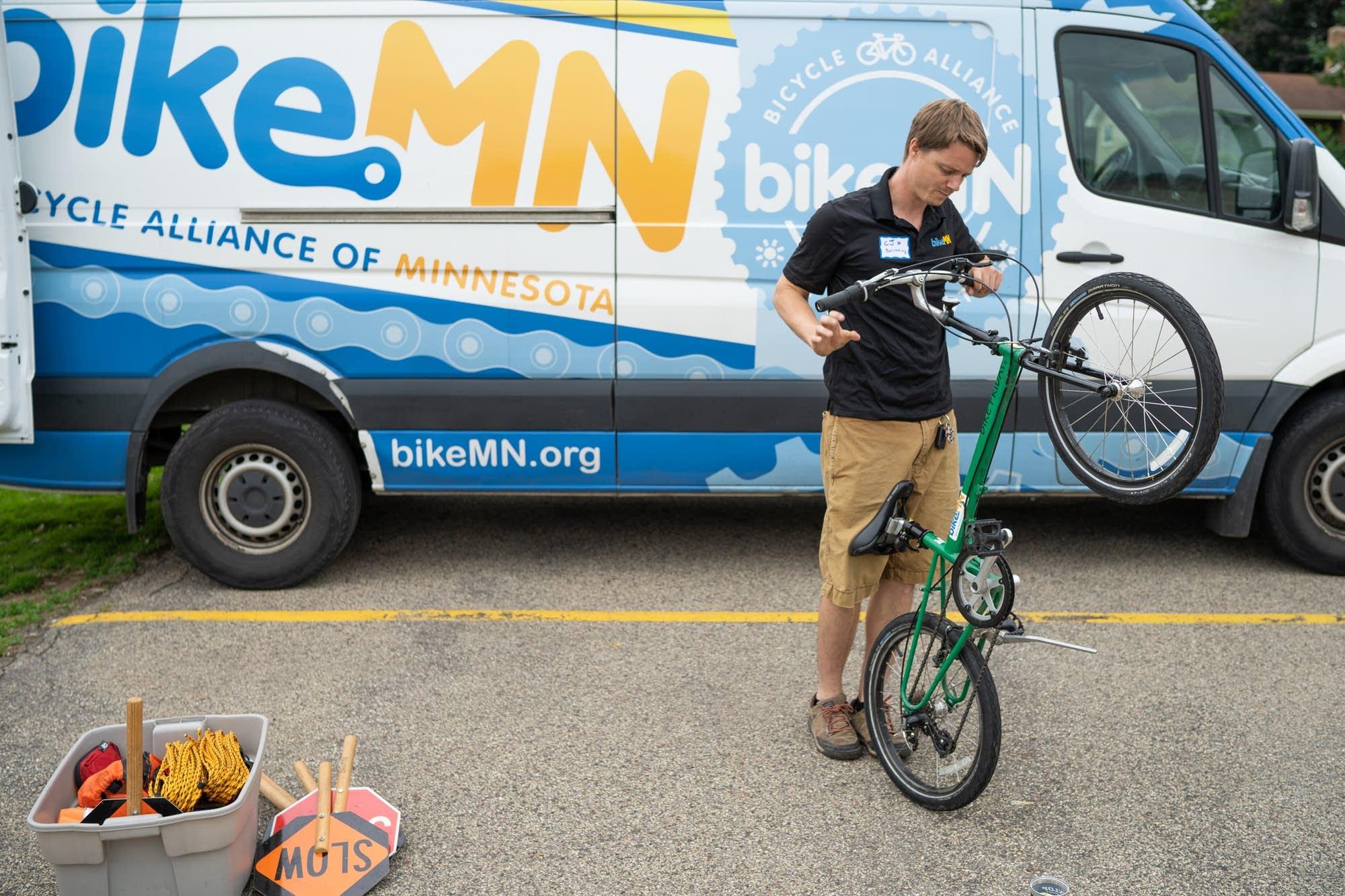 BikeMN education coordinator CJ Lindor inspects an adjustable bike.