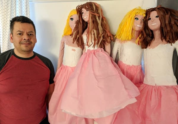 Victor Chavarria stands beside one of more than six bridesmaid pinatas.