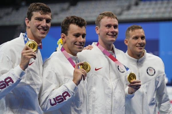 Four people hold up gold medals.