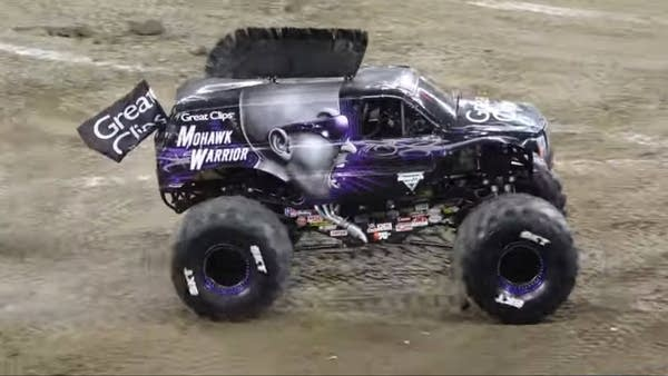 "Purple monster truck with a ""mohawk"" fin on top, performing in dirt"