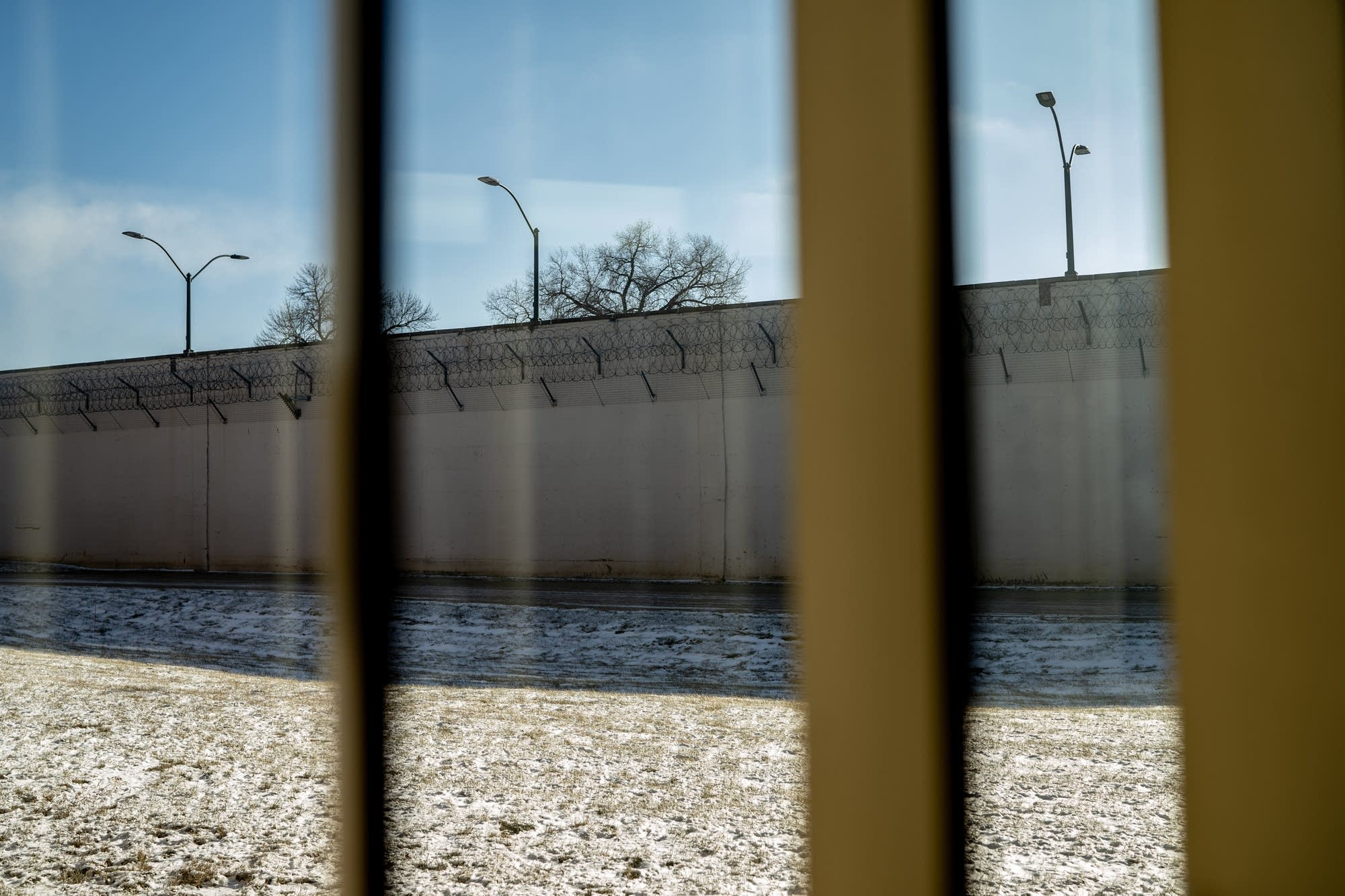 The prison wall is seen from a window across the hall from cells.