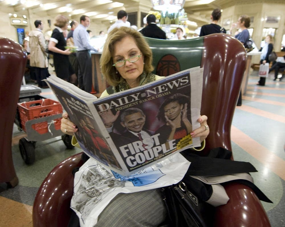 A woman reads a local newspaper November