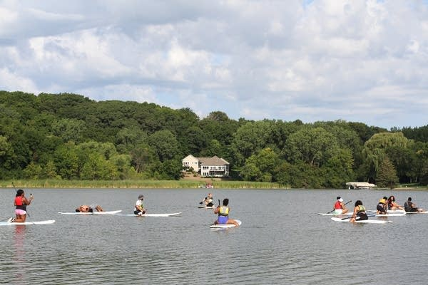 People sit on paddleboards in the lake.