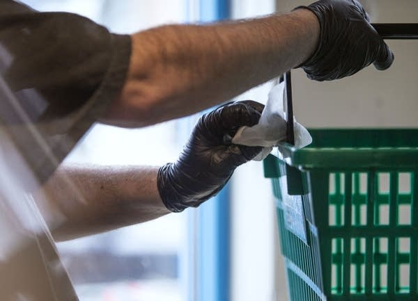 A person wearing gloves sanitizes a basket