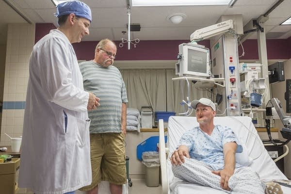 Andy Sandness, right, talks with his father and Dr. Samir Mardini