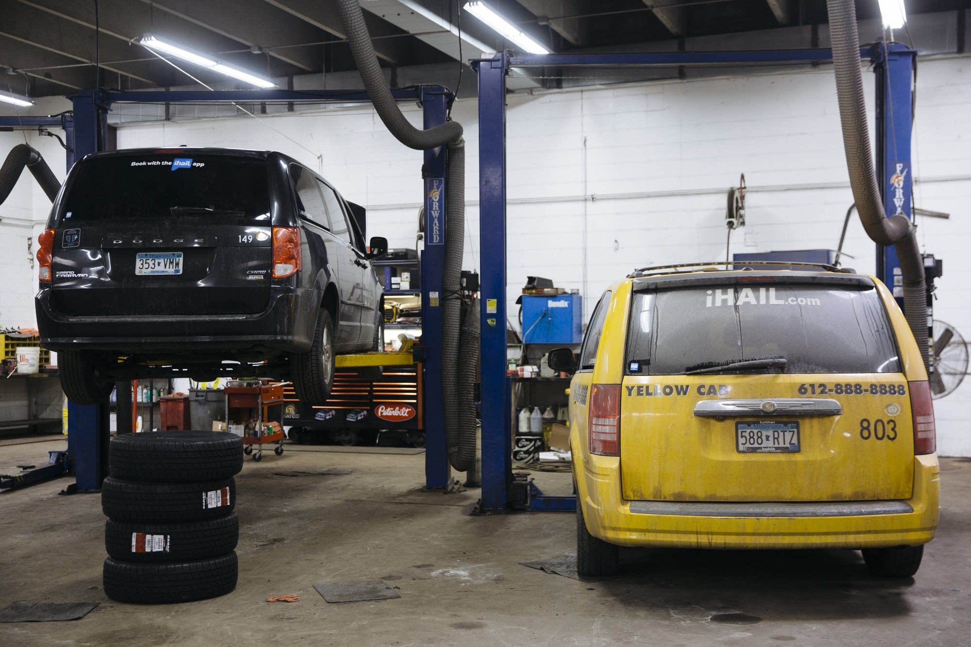 Two taxis are being worked on in the in shop of Taxi Services.