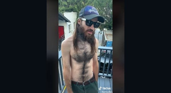 Shirtless white man with long hair, sunglasses and Planet Hollywood ballcap
