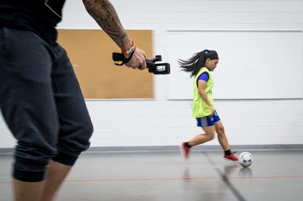 Coach Kyle Johnson films Hser Ku Wah, 15, during futsal practice.