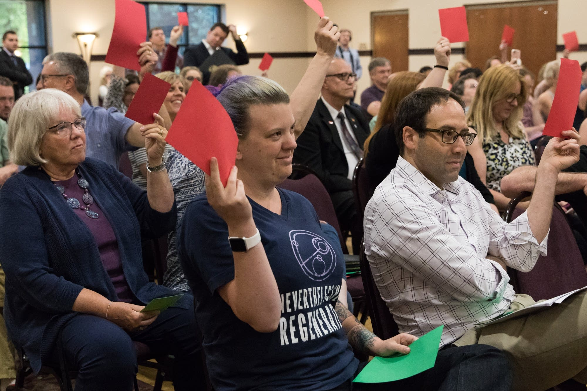 Town hall attendees raise red cards in the air to show they disagree.