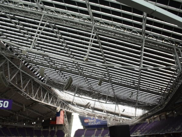 Crews install curtains between the roof trusses at US Bank Stadium