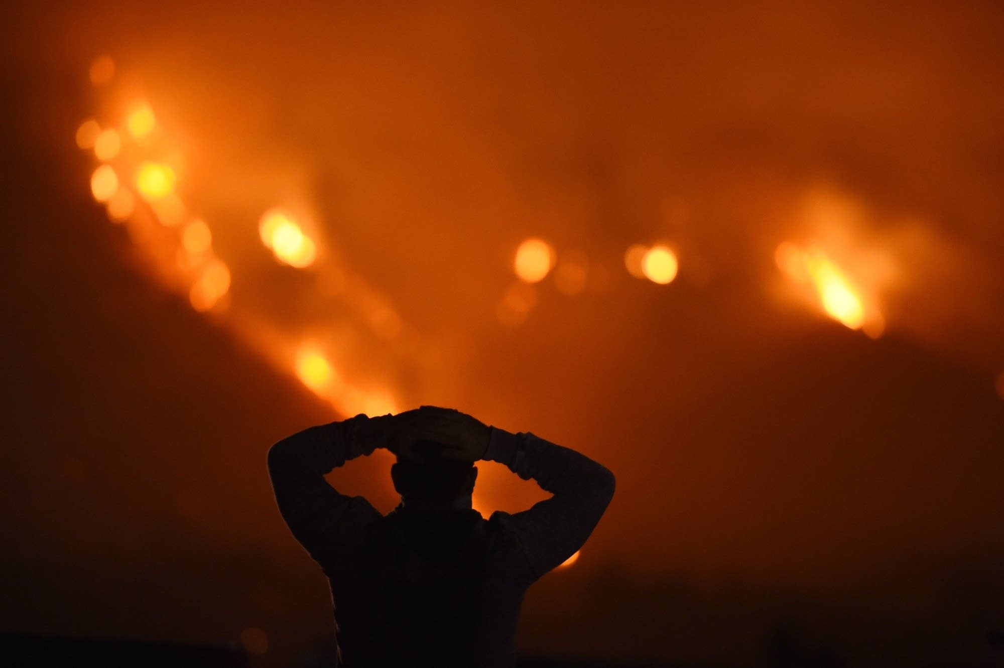 A man watches the Thomas Fire in the hills above Carpinteria, Calif.