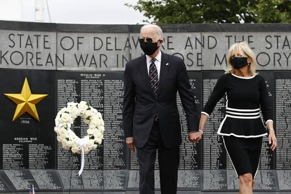 Two people wearing masks at a veterans memorial