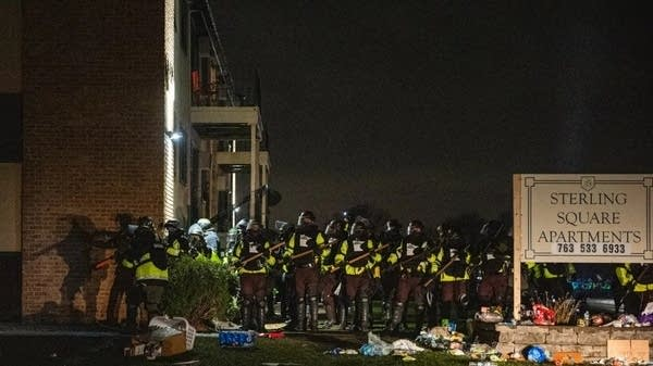 A large crowd of police in riot gear stand on near an apartment complex.