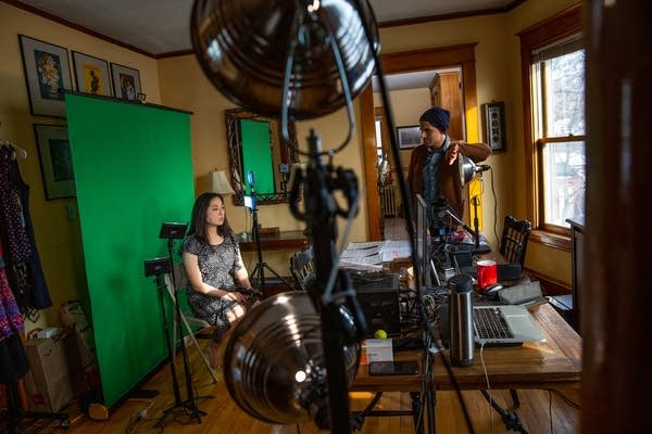 Two people stand in a dining room with lights and a green screen.