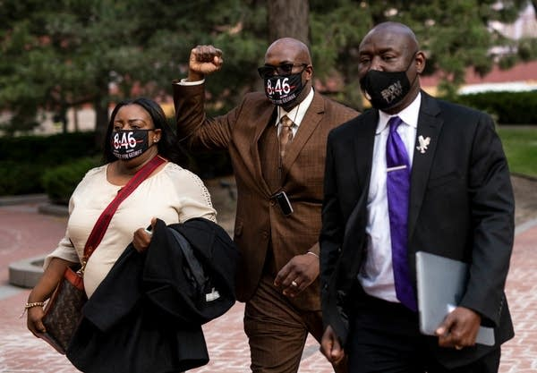 Three people wearing masks walk together.