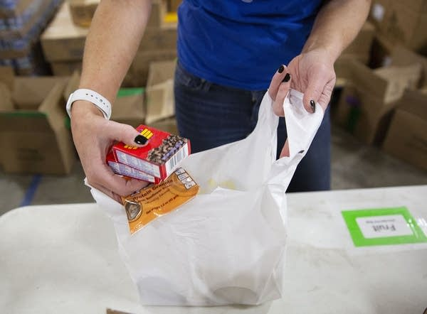 A close-up of hands putting food in a bag.