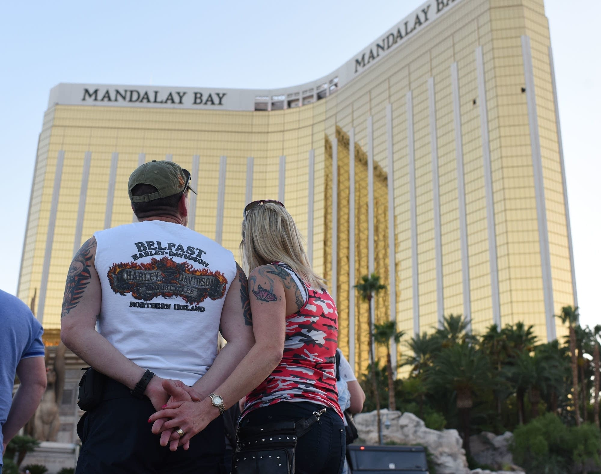 A couple looks up at the broken windows at the Mandalay Bay.