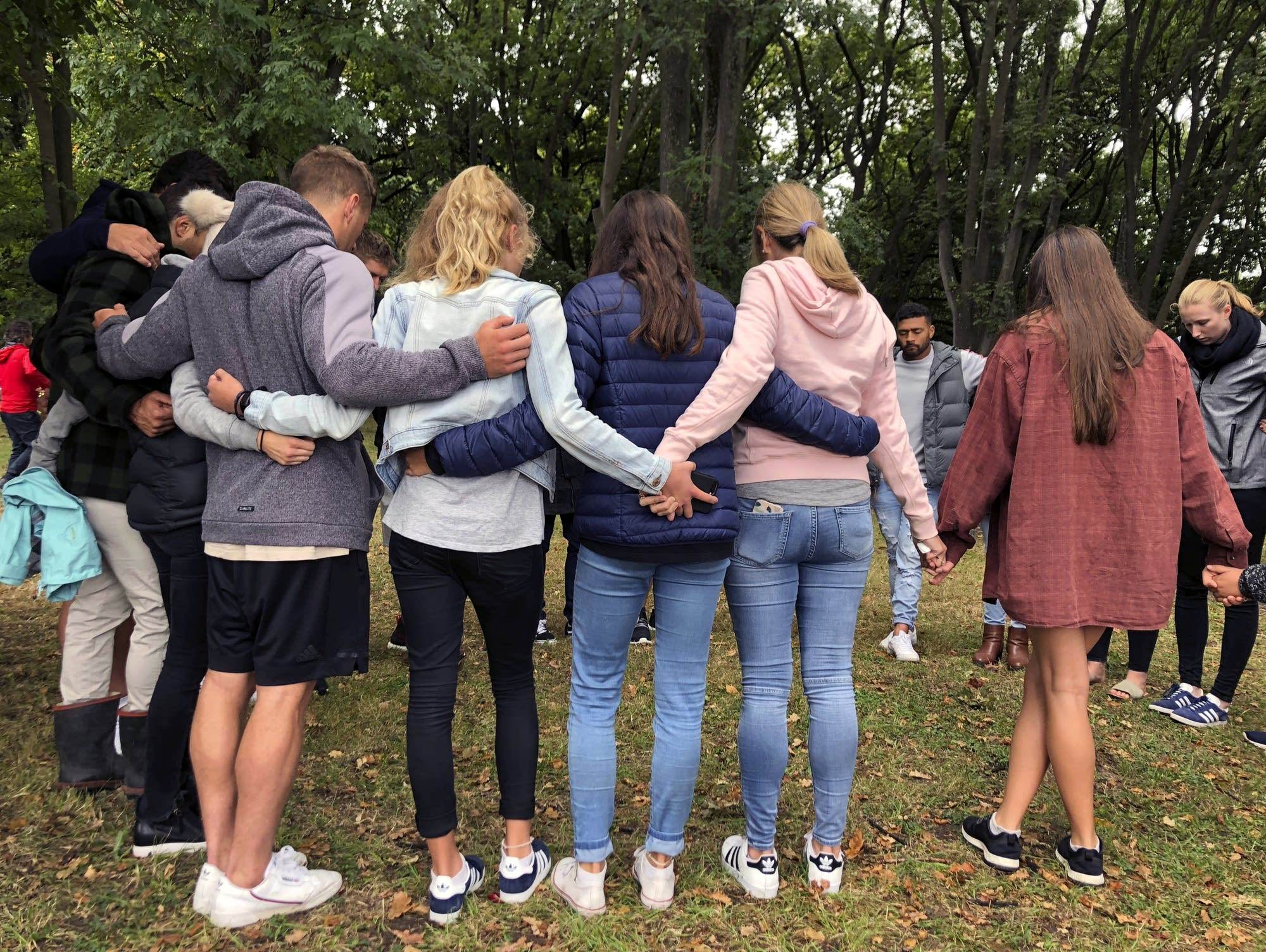 Mourners link arms in Hagley Park near the Al Noor mosque