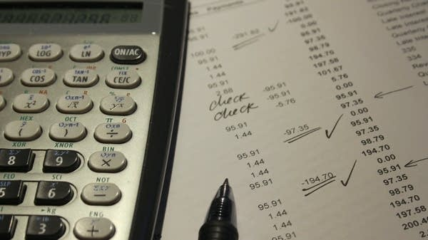 A calculator sits on top of a ledger of expenses.