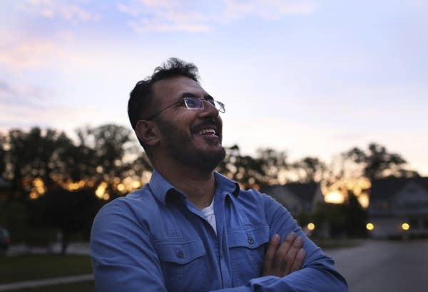 A man stands for a portrait in front of the setting sun.