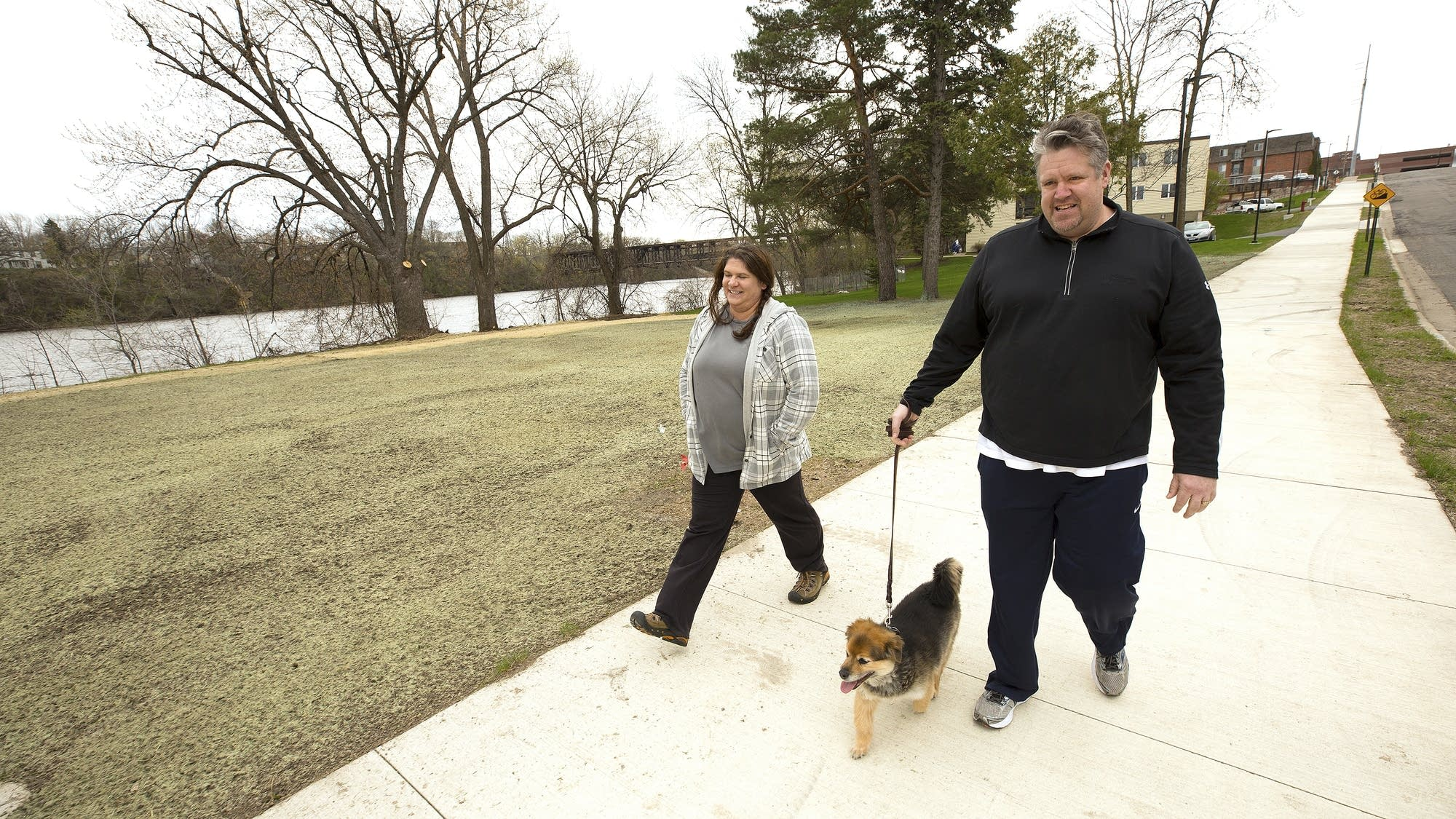 Stacy and Ryan Olson walk their dog, Trigger, near the new Butler Park.