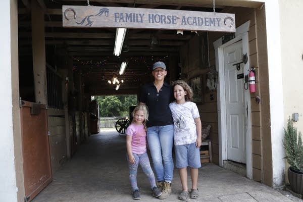 A woman and two children standing in a barn.