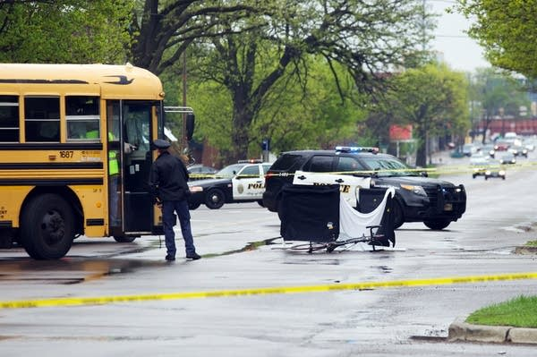 Police examine the scene of a crash between a school bus and a bicyclist.