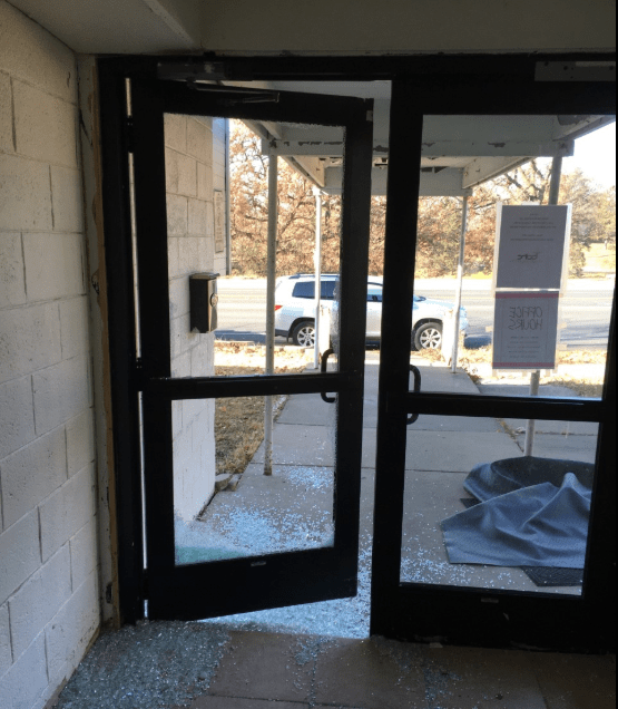 Glass is shattered in front of an entry door at the Salaam Cultural Center