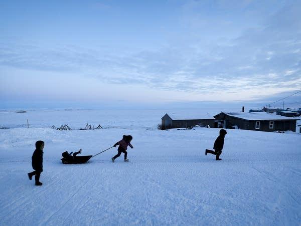 Children play in the snow Saturday in Toksook Bay, Alaska