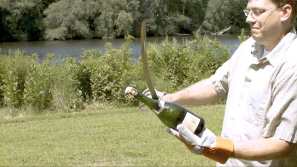 Man opening champagne bottle with saber