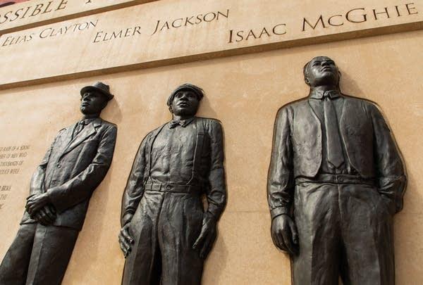 Sculptures of three people in relief.