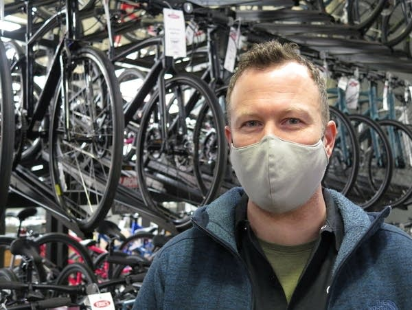 A man with a face mask stands in front of racks of bikes on display.