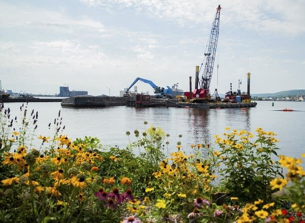 A barge floating in the water with wildflowers growing in the foreground.