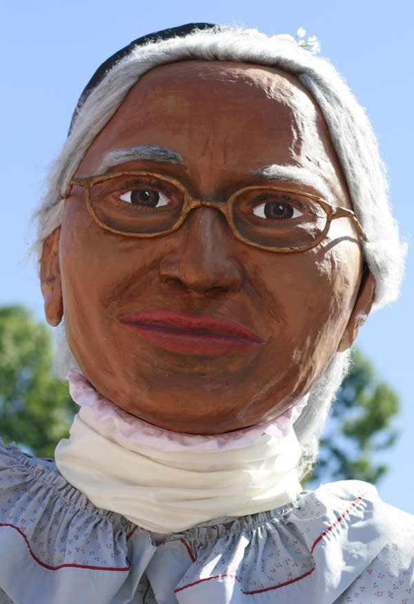 A protester in an oversized Rosa Parks costume
