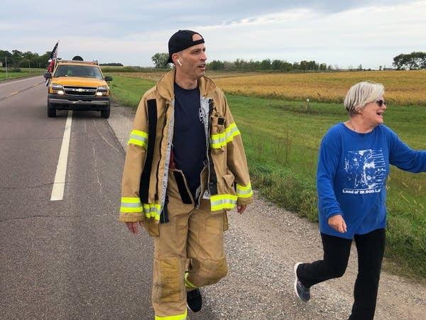 A firefighter walks along a highway