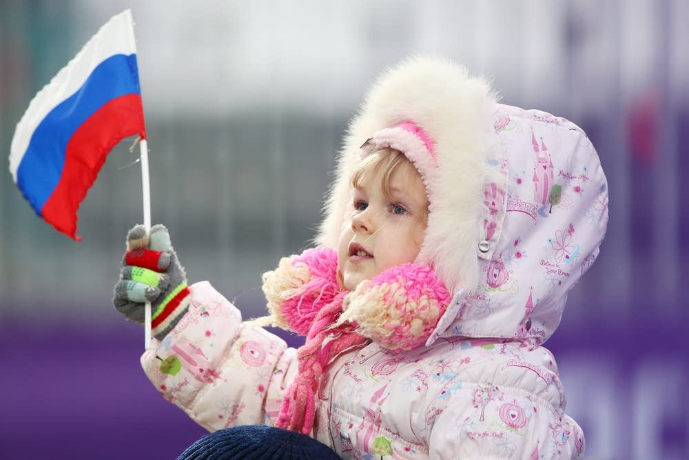 A young child watches freestyle skiing