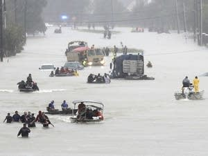 Rescue boats fill a flooded street.