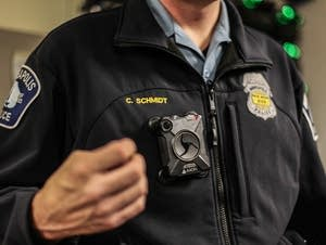A Minneapolis police officer shows body cameras