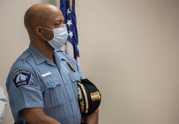 A man wearing a police uniform and a face mask.