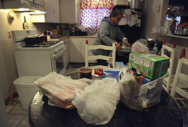 Bags of food from a local church pantry sit on a kitchen table.