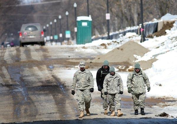 National Guard walk  along a dike in Fargo