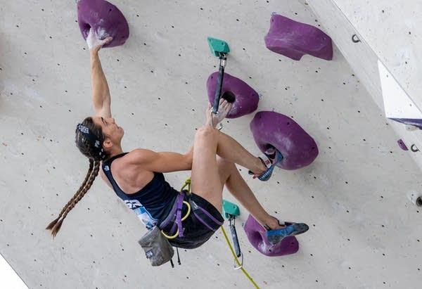 A woman climbs a wall.