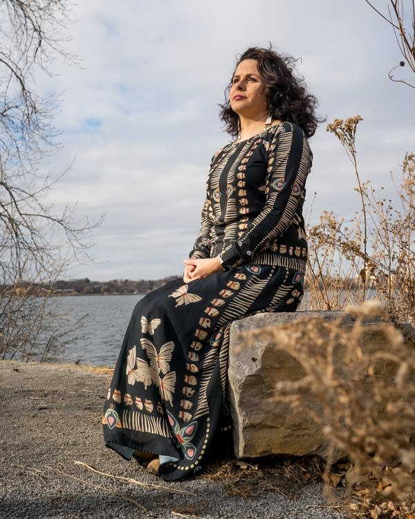 A woman in a patterned dress sits on a rock in front of a lake.