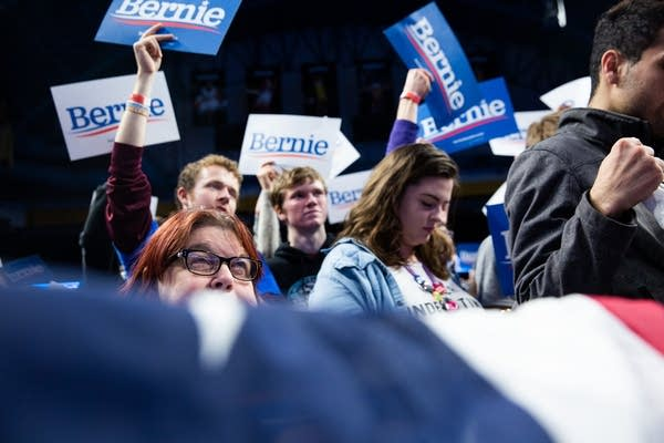 People look up at a stage over a banner.