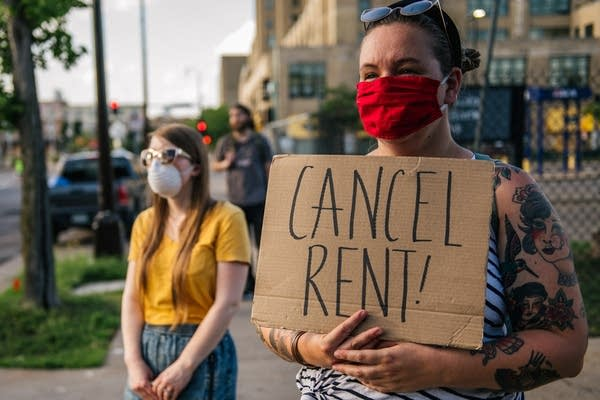 "A demonstrator holds a sign that reads ""Cancel Rent!"""
