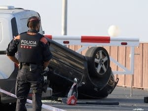 A police officers stands by a car involved in a terrorist attack.