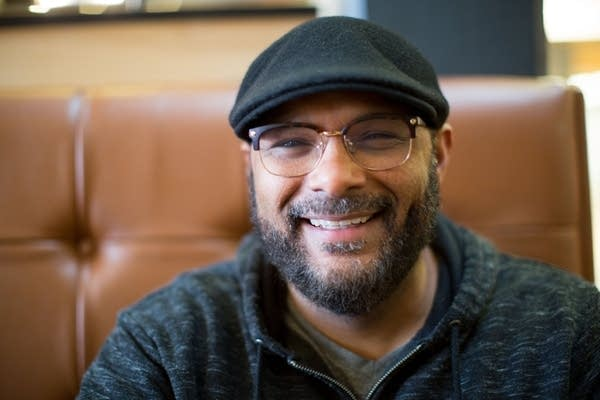 A person smiling while wearing glasses and a hat.