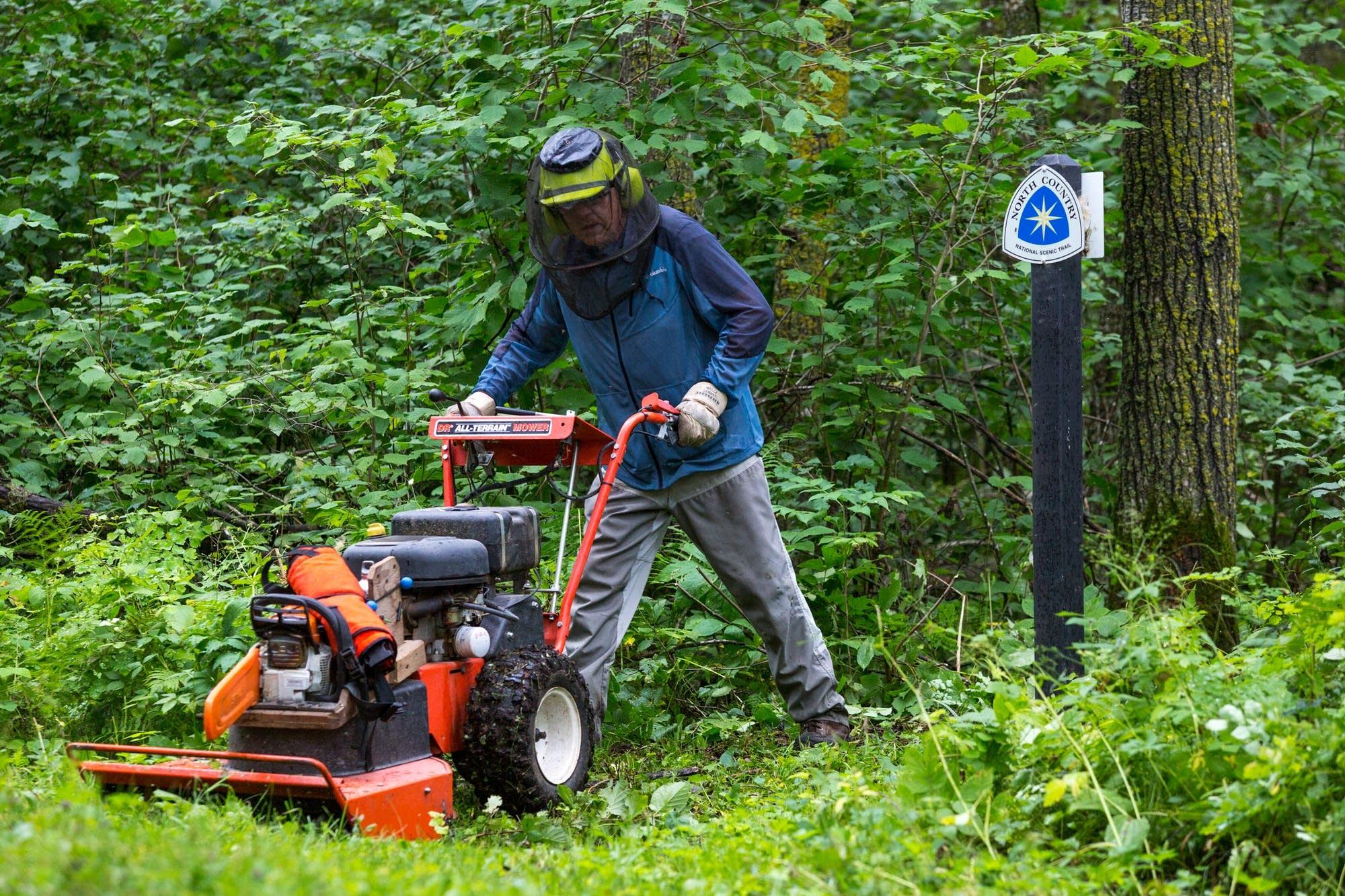 Jim Rakness pushes a mower