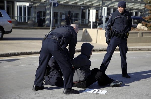 A protester is arrested for blocking the roadway.